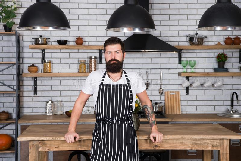 He is a champion in the kitchen. Hipster in kitchen. Mature male. Bearded man cook. Bearded man in apron. Man chef. Cooking. Restaurant or cafe cook. Lunch time royalty free stock photo