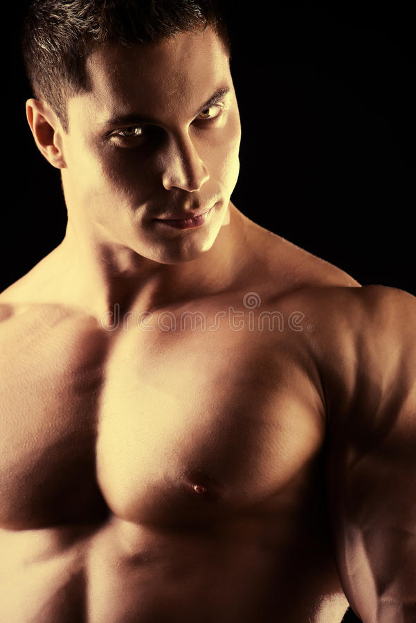 Champion male. Close-up shot of a handsome muscular bodybuilder posing over black background stock photos