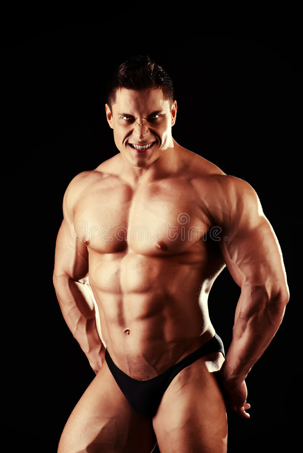 Champion male. Handsome muscular bodybuilder posing over black background stock photos