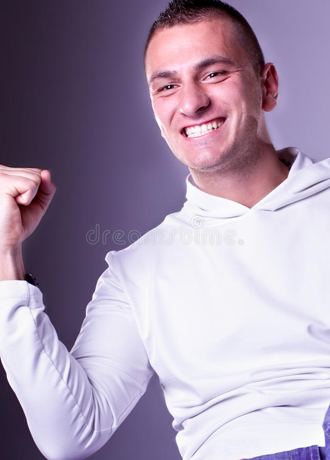 Champion man with fists clenched in victory. Champion man standing with fists clenched in victory.Close up studio shot stock images