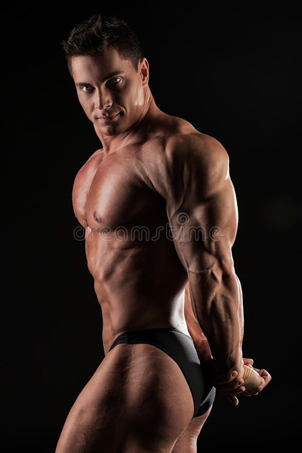 Champion man. Handsome muscular bodybuilder posing over black background royalty free stock photography