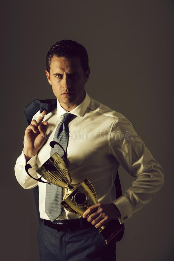 Champion man holding golden winner cup. Champion man, successful businessman or manager holding golden winner cup in fashion white shirt, tie and jacket on stock images