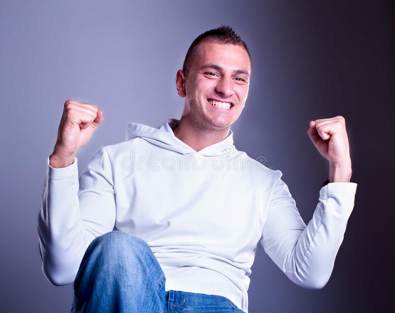 Champion man standing with fists clenched. In victory. Studio shot stock images