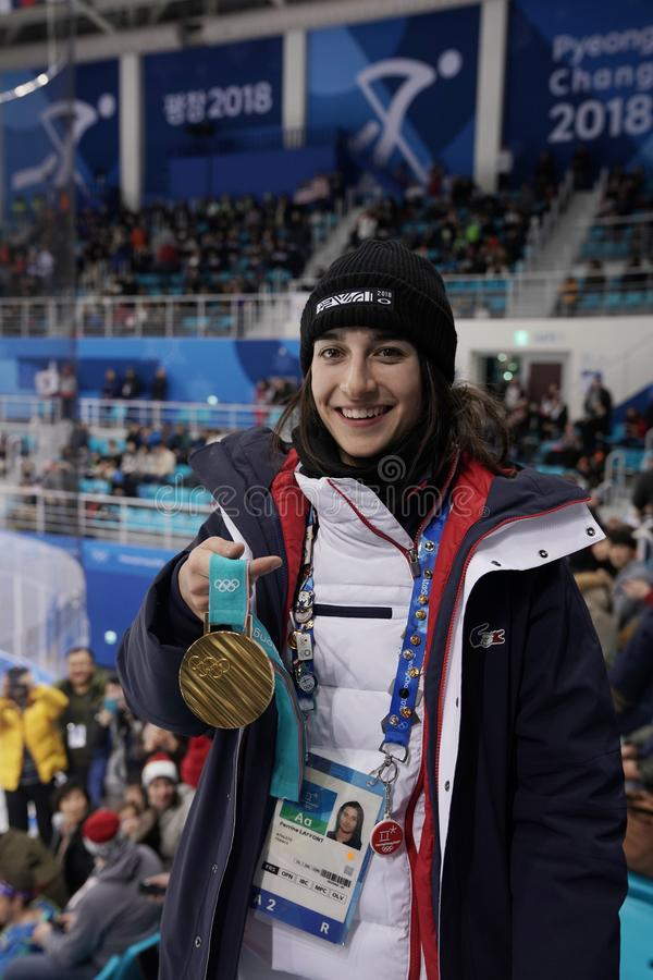 Champion olympique dans des nababs Perrine Laffont de ` de dames des Frances posant avec la médaille d'or image libre de droits