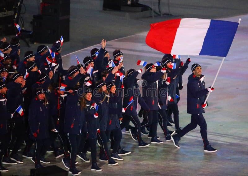 Champion olympique Martin Fourcade portant le drapeau français menant les Frances olympiques d'équipe pendant s'ouvrir de 2018 Je image stock