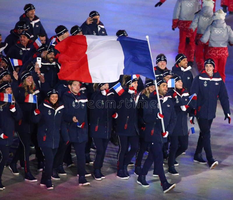 Champion olympique Martin Fourcade portant le drapeau français menant les Frances olympiques d'équipe pendant s'ouvrir de 2018 Je images stock