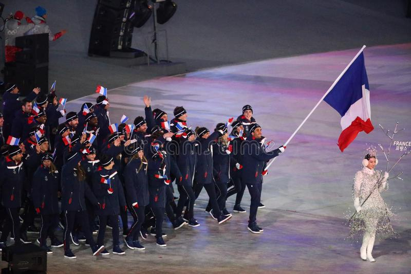 Champion olympique Martin Fourcade portant le drapeau français menant les Frances olympiques d'équipe pendant s'ouvrir de 2018 Je photos stock