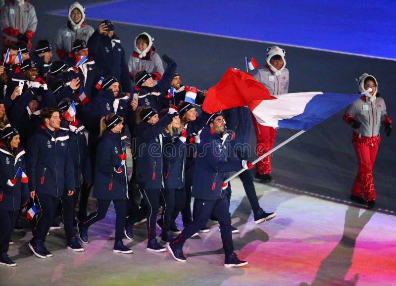 Champion olympique Martin Fourcade portant le drapeau français menant les Frances olympiques d'équipe pendant s'ouvrir de 2018 Je photo stock