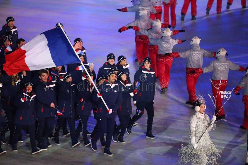 Champion olympique Martin Fourcade portant le drapeau français menant les Frances olympiques d'équipe pendant s'ouvrir de 2018 Je photographie stock