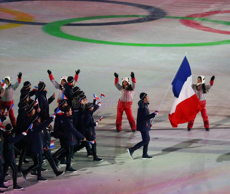 Champion olympique Martin Fourcade portant le drapeau français menant les Frances olympiques d'équipe pendant s'ouvrir de 2018 Je photos libres de droits