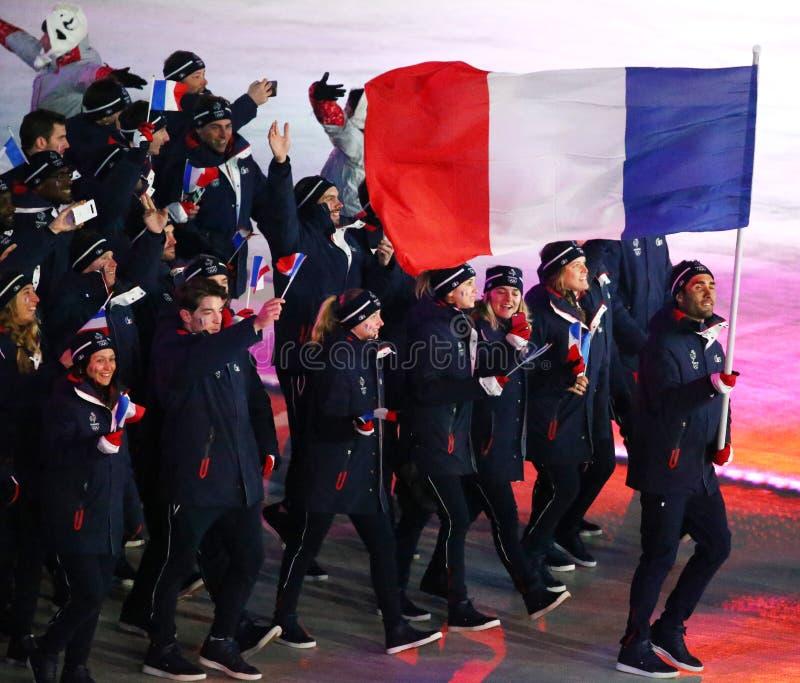 Champion olympique Martin Fourcade portant le drapeau français menant les Frances olympiques d'équipe pendant s'ouvrir de 2018 Je photographie stock libre de droits