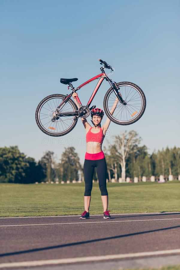 Champion! Powerful athlete is lifting her modern bike above the stock photography