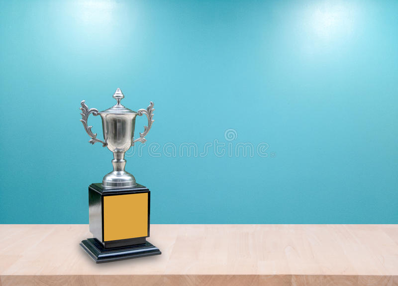 Champion silver trophies on wood table with lighting victory. (business success and sport success concept) royalty free stock photos
