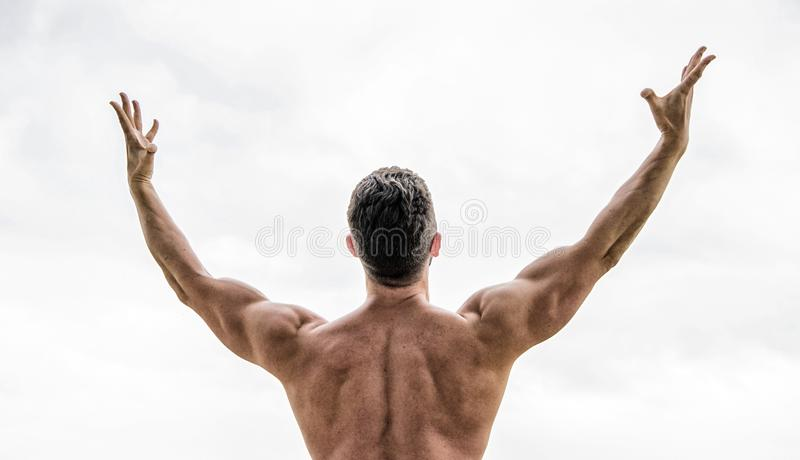 Champion and winner concept. Man celebrating success. Bodybuilder strong muscular body feeling powerful and superior. Rear view. Achieve success. Great shape royalty free stock image