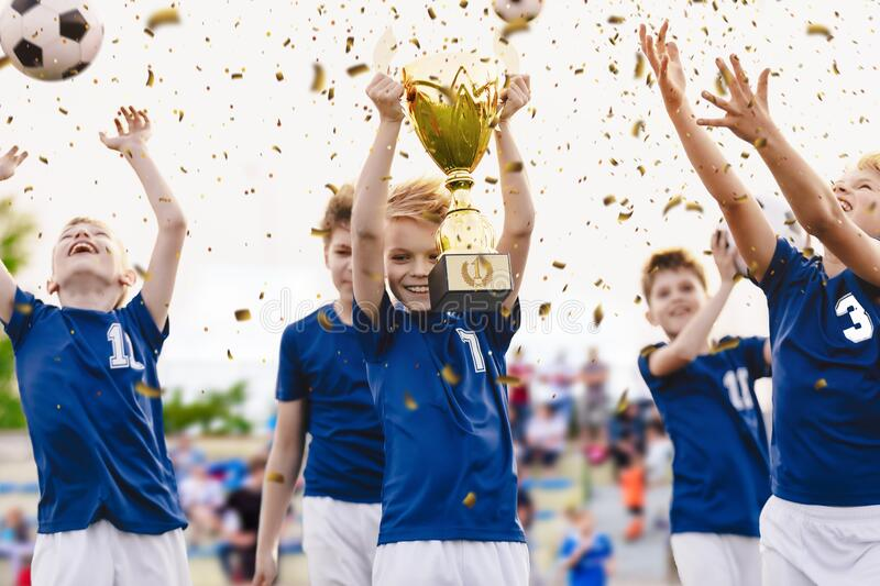 Champion youth soccer team with winning trophy. Boys football team celebrating victory in school competition stock image