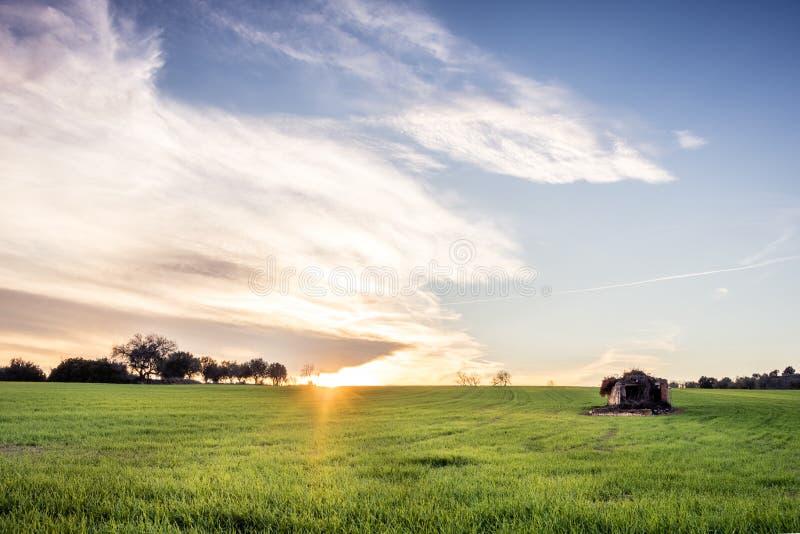 Champs au coucher du soleil avec une petite maison photos stock