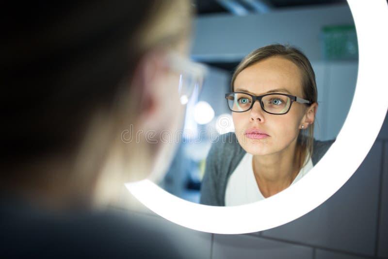 Chancelant, jeune femme baîllant devant son miroir de salle de bains photo stock