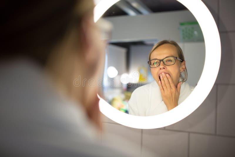 Chancelant, jeune femme baîllant devant son miroir de salle de bains photographie stock