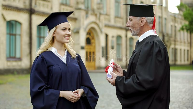 Chancellor of university giving diploma to graduating student, successful future. Stock photo royalty free stock photos