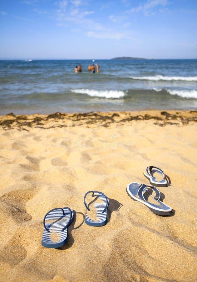 Chancleta azul de la sandalia en la playa de la arena y el grupo de jugar a gente en la distancia en el agua foto de archivo libre de regalías