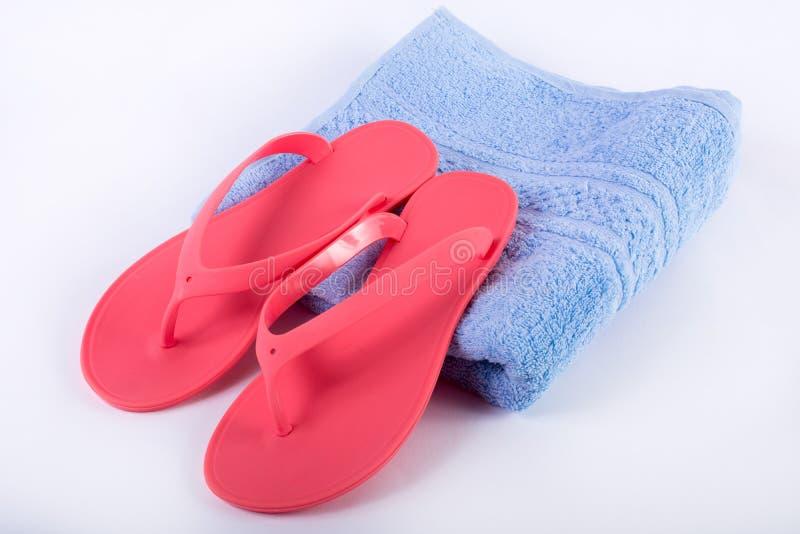 Chancleta rosada de la sandalia en la toalla azul y el fondo blanco foto de archivo libre de regalías