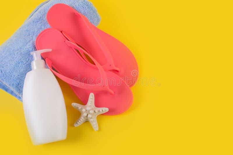 Chancleta rosada de la sandalia en la toalla azul y la loción y las estrellas de mar poner crema del bronceado en fondo amarillo fotografía de archivo