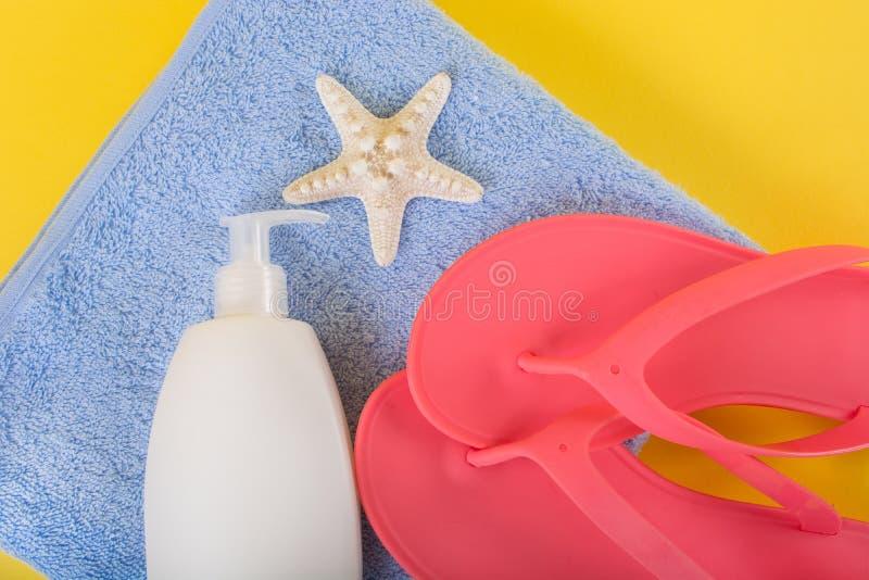 Chancleta rosada de la sandalia en la toalla azul y la loción y las estrellas de mar poner crema del bronceado en fondo amarillo imagenes de archivo