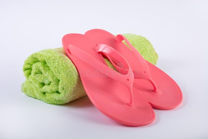 Chancleta rosada de la sandalia en la toalla verde y el fondo blanco imágenes de archivo libres de regalías