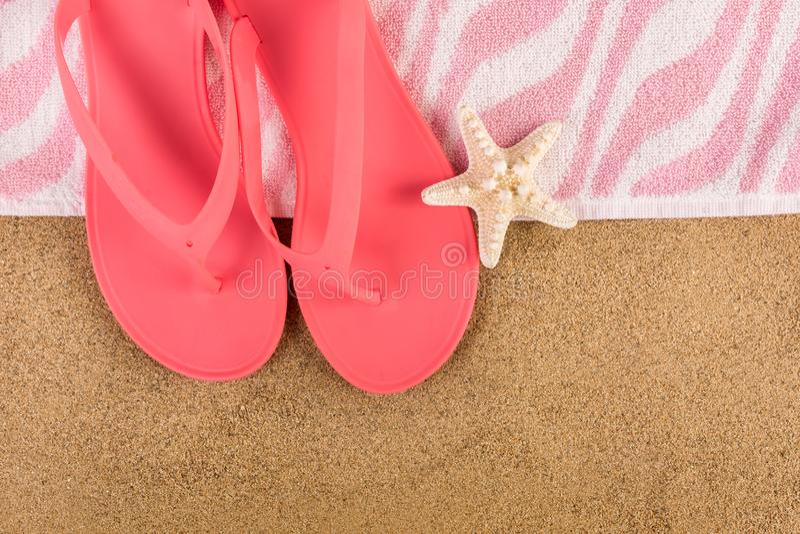 Chancleta rosada y toalla de la sandalia en la playa y estrellas de mar de la arena fotografía de archivo