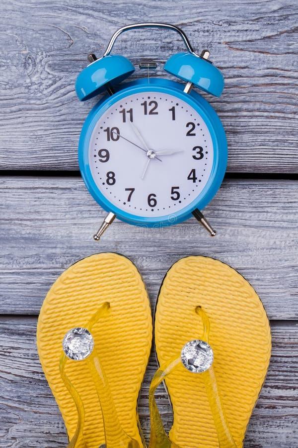 Chancletas amarillas y despertador azul imagen de archivo libre de regalías