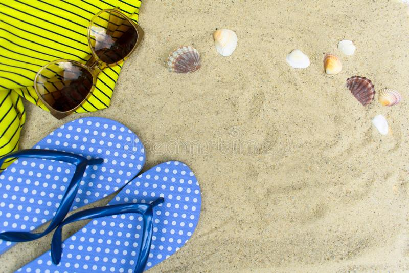 Chancletas azules, gafas de sol en la playa arenosa con las conchas marinas imágenes de archivo libres de regalías
