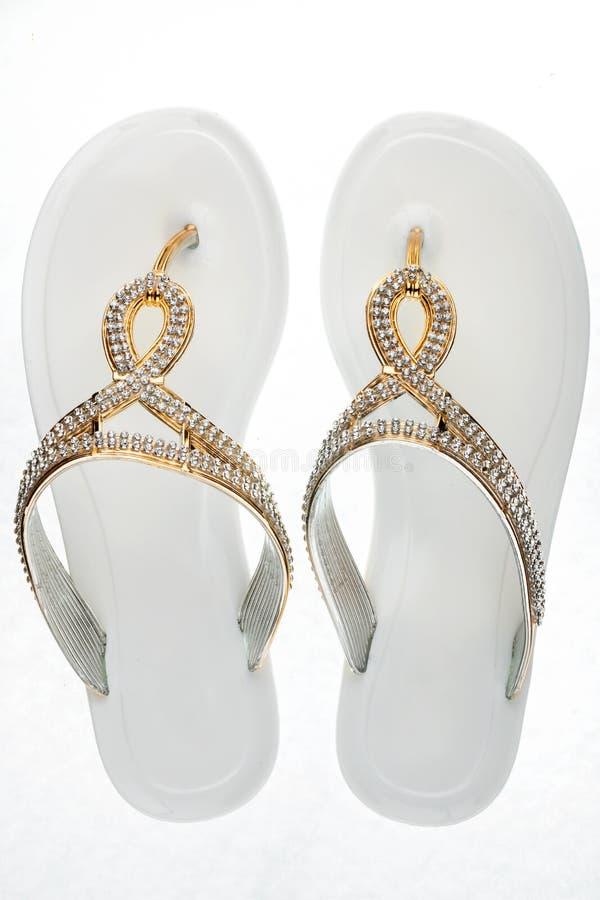 Chancletas blancas atractivas, sandalias adornadas con los diamantes artificiales en un fondo blanco foto de archivo