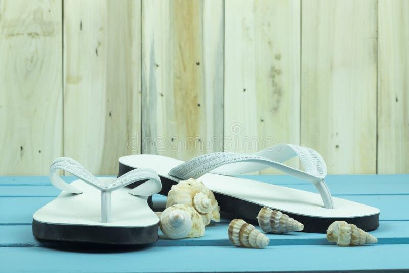 Chancletas blancas con los shellfishs en la tabla de madera azul fotografía de archivo