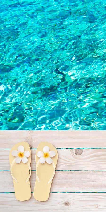 Chancletas con las flores del tiare en el decking de madera de los tablones sobre fondo borroso mar de la turquesa foto de archivo libre de regalías