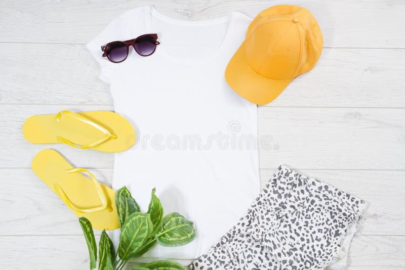 Chancletas femeninas blancas de la camiseta falsas encima de endecha del plano en fondo de madera Espacio de la visi?n superior y imágenes de archivo libres de regalías
