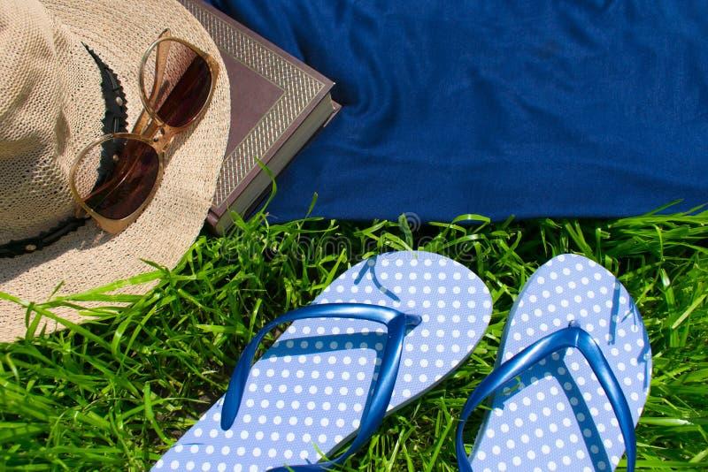Chancletas, sombrero del verano, libro y gafas de sol en la hierba verde fotografía de archivo libre de regalías