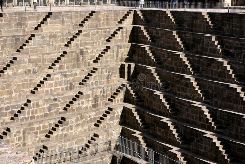Chand Baori Step Well. India. India village of Abhaneri is in it a reservoir for rainwater. The stone stairs lay into a mystical, deceptive space. Fantastic royalty free stock photo