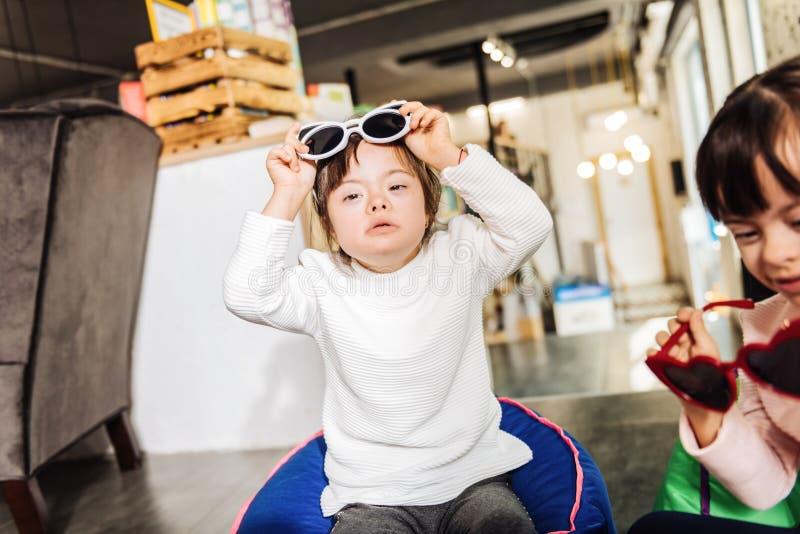 Chandail blanc de port et lunettes de soleil d'enfant ensoleillé aux yeux noirs mignon images libres de droits