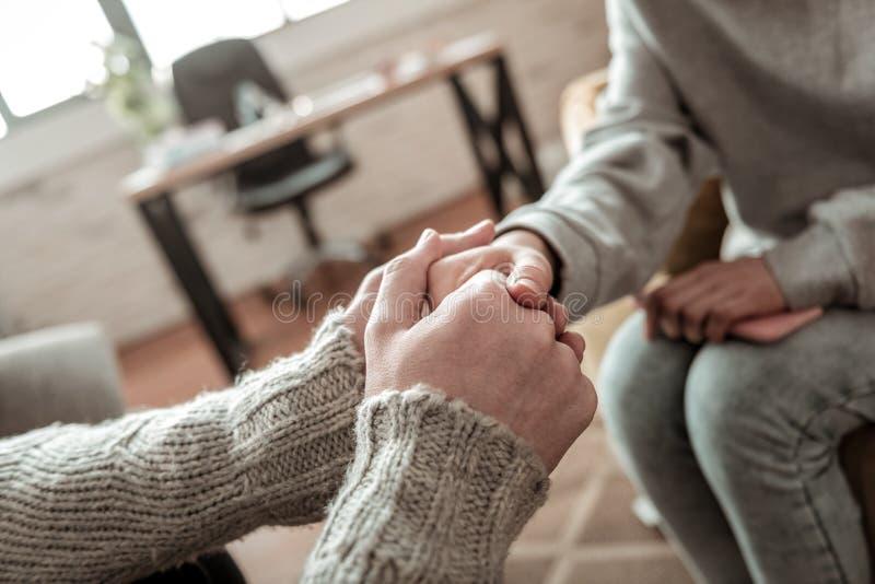 Chandail de port de père serrant la main de la fille après entretien image libre de droits