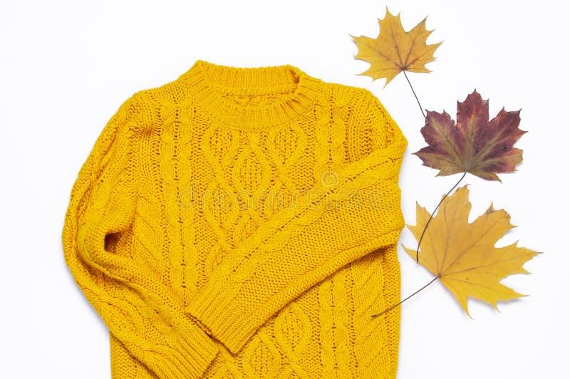 Chandail et feuilles d'automne tricotés oranges femelles sur la configuration plate blanche de vue supérieure de fond Madame Clot photographie stock libre de droits