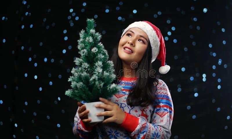 Chandail et Santa Hat Holding Small de port de Noël de fille asiatique photo libre de droits