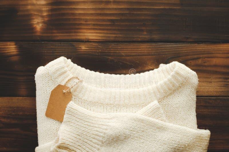 Chandail tricoté blanc avec le prix à payer sur la vue supérieure de vieux fond en bois Madame Clothes Set Trendy de mode confort photographie stock libre de droits