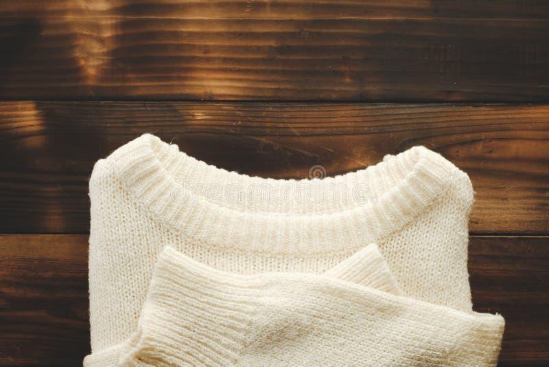 Chandail tricoté blanc sur la vue supérieure de vieux fond en bois Madame Clothes Set Trendy de mode confortable tricotent image libre de droits