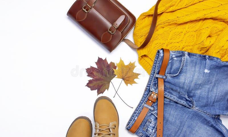 Chandail tricoté orange femelle, blues-jean, sac en cuir, bottes et feuilles d'automne sur la configuration plate blanche de vue  images libres de droits