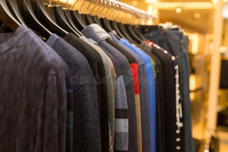 Chandails et chemises d'hommes dans différentes couleurs sur des cintres dans un magasin détaillant de vêtements image libre de droits