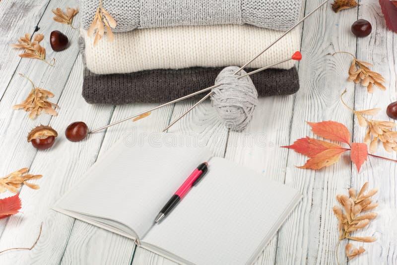 Chandails tricotés de laine La pile de l'hiver tricoté, automne vêtx sur le fond en bois, chandails, tricots, stylo, livre, l'esp images libres de droits