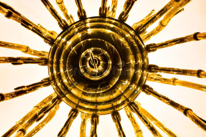 Chandelier abstract. This is the underside of the chandelier that hangs in the main hall of the apartment complex I live in. The brass coating and the way the stock photo