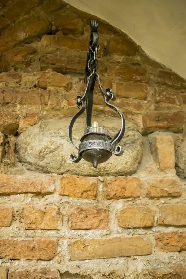 Chandelier antique contre le mur de briques rouge du château images stock