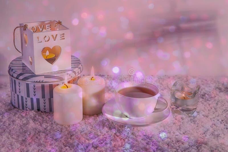 Chandelier blanc en bois, bougies, tasse de thé et cheval en bois sur la neige artificielle blanche images stock
