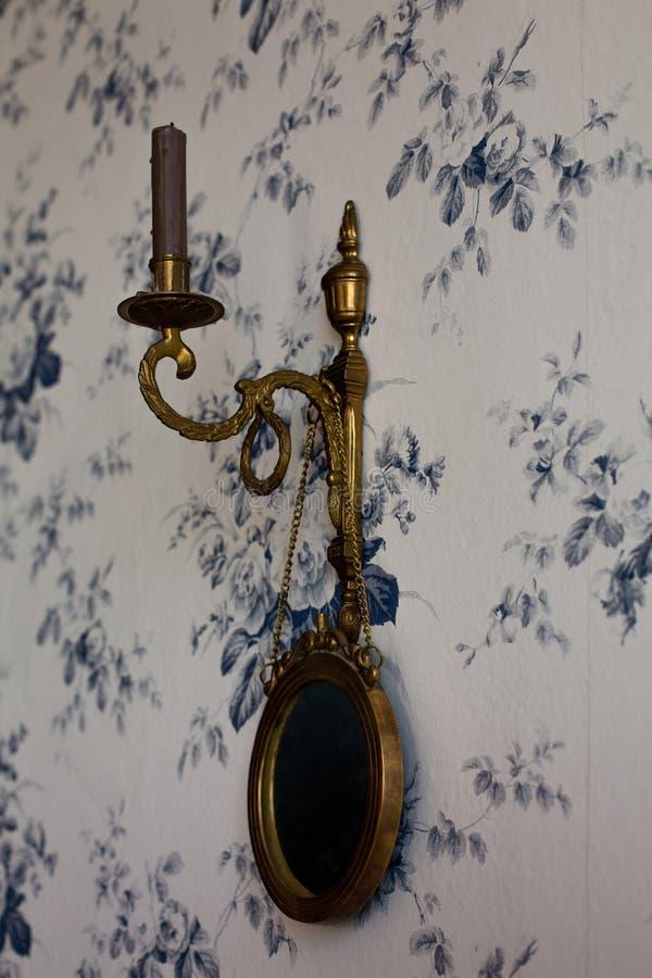 Chandelier de cuivre avec un miroir accrochant sur le mur photo stock